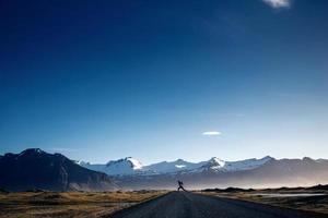 homem pulando na estrada sinuosa da montanha