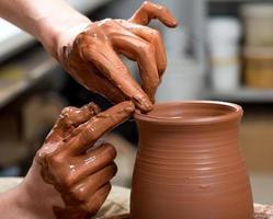 mãos do oleiro, criando um pote de barro