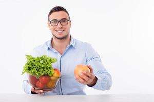 Attractive young guy is eating healthy food photo