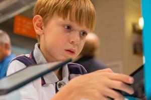 kind (7-8 jaar) spelen met tablet-computer in een winkel