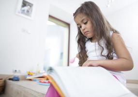 schattig meisje leesboek thuis