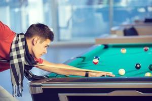 joven jugando billar en el club de billar foto