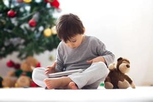 Cute little boy and his monkey toy, playing on tablet
