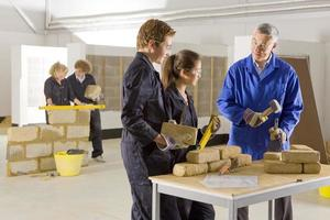 Teacher teaching students bricklaying in vocational school photo