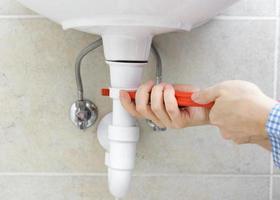 Plumber is r repairing sink In Bathroom photo