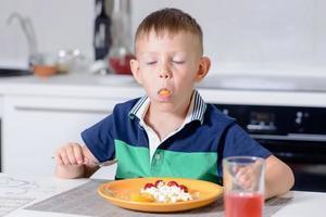 Chico con la boca llena comiendo queso y fruta foto