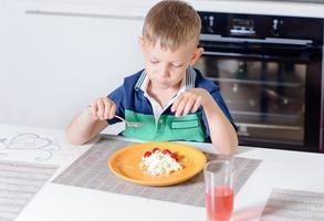 jonge jongen die plaat van kaas en fruit eet