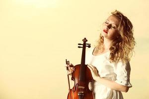 het blonde meisje met een viool buiten