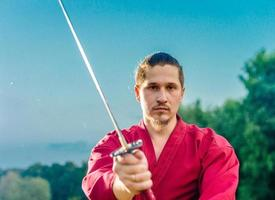 Hombre en uniforme de ropa japonesa samurai étnico con espada katana