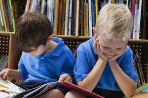 Two children wearing blue shirts reading in a library