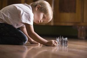 Niño jugando con soldados de juguete en el piso