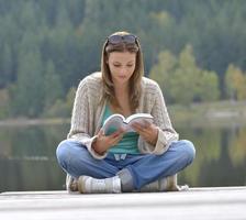 libro de lectura de mujer joven cerca de un lago