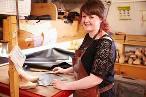 Young shoemaker working with leather in a workshop, portrait photo