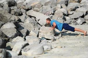 The young man carries out push-ups among stones photo