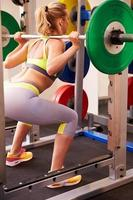 Woman weightlifting barbells at a squat rack in a gym