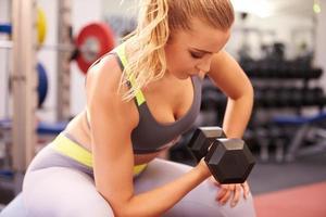 Mujer joven haciendo ejercicio con pesas en un gimnasio, horizontal