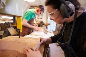 zapateros que cortan y dan forma a la madera para hacer hormas foto