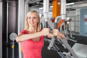 Cheerful fit girl is exercising with the equipment in gym photo