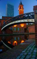 Old bridge over canal and modern architecture in Manchester UK photo