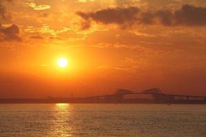 hermosa puesta de sol en el puente de la puerta de tokio y la bahía de tokio foto