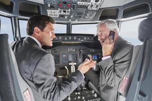 empresarios volando avión usando teléfono móvil al mismo tiempo foto