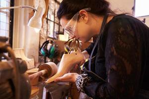 Shoemaker sanding shoe lasts in a workshop photo
