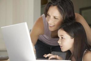 madre ayudando a la hija a usar la computadora portátil foto