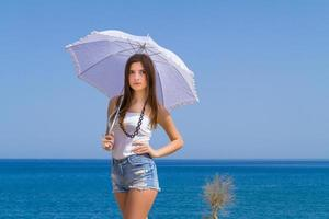 Young beautiful brunette with white umbrella enjoys the summer