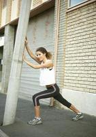Runner stretching against pole