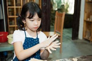 niño asiático formando cerámica