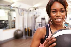 Portrait of a smiling woman holding a medicine ball
