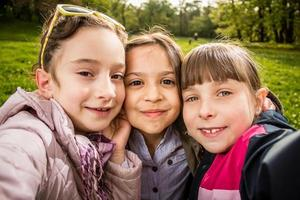 Photo of three girls making selfie close up