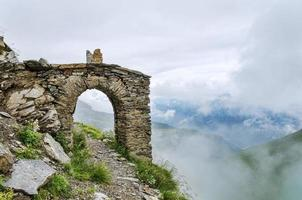Old arch construction and mountain hiking path going through photo
