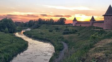 The castle wall at the river at sunset. photo