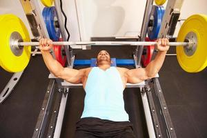 Man flexing muscles while bench pressing weights at a gym