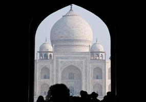 taj mahal seen through an archway