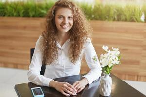Indoor shot of lovely young woman with curly long hair, comes in restaurant to meet with colleague, wears formal blouse, uses mobile phone for online communication. People and positiveness concept photo