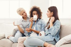 Three young female friends with coffee chatting at home
