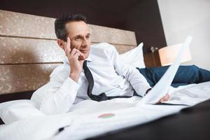 Businessman on bed reading paperwork photo
