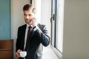 apuesto hombre de negocios hablando por teléfono inteligente en la habitación del hotel y mirando a cámara