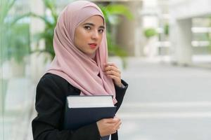 Beautiful Malay girl holding books outdoor