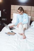 mujer de negocios usando la computadora portátil en la habitación del hotel