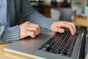 Primer plano del brazo masculino, escribiendo en la computadora portátil, búsqueda de empleo, trabajo en línea, en un café con una computadora portátil, con los dedos presionando el botón