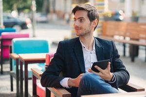 Retrato joven sosteniendo la tableta en la mano. foto