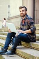 Un hombre usando una laptop. foto