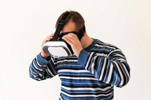 Man wearing and playing mobile game app on device virtual reality glasses on white background. Man action and using in virtual headset, VR box for use with smart phone. Contemporary technology concept photo