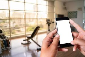 Young man Hand holding smartphone in gym to  fitness phone fitness exercise concept