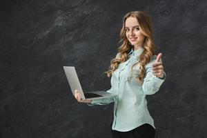 Happy woman with laptop on gray background