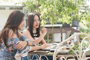 Dos mujeres adolescentes se reúnen en una cafetería usan la computadora portátil juntas en la tarde, estilo de vida del nuevo adolescente foto