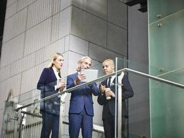 three corporate executives discussing business using digital tablet